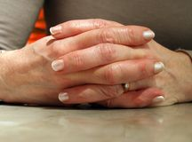 Woman's Hands linked on table Stock Image