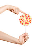 Woman's hands with lollipop Stock Image