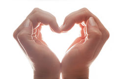 Woman's hands make a heart shape on white background, backlight. Love Royalty Free Stock Images