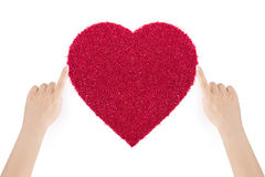 Woman's hands making the heart of red sand by index fingers. Stock Image