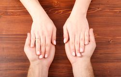 Woman's hands on man's hands. On wooden table stock photography