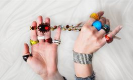 Woman`s hands with many colorful glass rings, bracelet and nekla. Woma`s hands with many colorful glass rings, bracelet and neklace on a white cloth. Close up Royalty Free Stock Photo