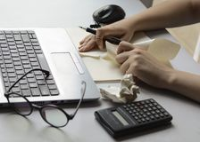 Woman`s hands at the office desk are splitting paper in front of the laptop. stock images