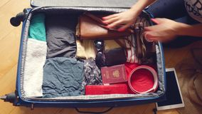 Woman's hands are packing suitcase for a journey and dreaming about traveling. 3840x2160. 4k. Woman's hands are packing suitcase for a journey stock video footage