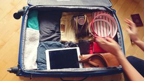 Woman's hands are packing suitcase for a journey. Dreams about travel. 3840x2160. Woman's hands are packing suitcase for a journey stock video footage