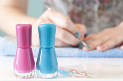 Woman's hands painting her nails with blue nail polish Stock Image