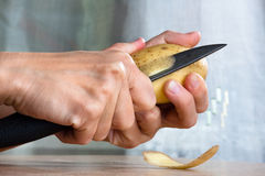 Woman's hands peeling potatoes with knife Royalty Free Stock Photography