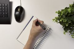 Woman`s hands with pen writing on notebook. Modern grey office d royalty free stock images
