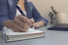 Woman`s hands with pen writing on notebook. Modern grey office d royalty free stock photography