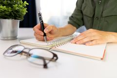 Woman`s hands with pen writing on notebook. Modern office desk. royalty free stock images