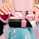 Woman`s hands with pink manicure holding black present box. With pink tape Stock Photo