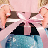 Woman`s hands with pink manicure holding black present box. With pink tape Royalty Free Stock Photography