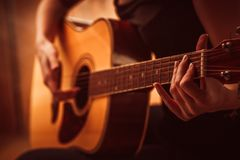 Woman's hands playing acoustic guitar, close up Stock Image