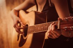 Woman's hands playing acoustic guitar, close up Stock Photos