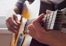 Woman's hands playing acoustic guitar Stock Photos