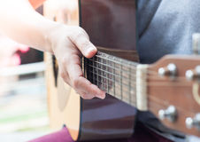 Woman's hands playing acoustic guitar Stock Photography