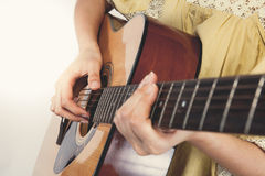 Woman's hands playing guitar, close up. Vintage tone Royalty Free Stock Images