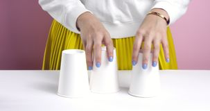 Woman playing tricks with paper cups. Woman`s hands playing with 3 paper cups hiding a ball of foil under one and then switching them around stock video