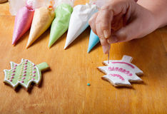 Woman's hands in process of drawing on new year gingerbread cook Royalty Free Stock Images