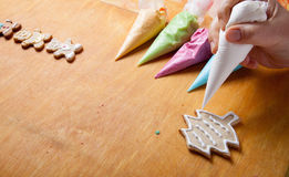 Woman's hands in process of drawing on new year gingerbread cook Royalty Free Stock Photos