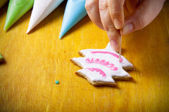 Woman's hands in process of drawing on new year gingerbread cook Stock Photo