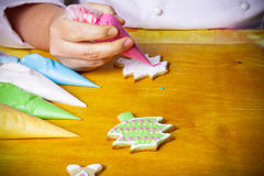Woman's hands in process of drawing on new year gingerbread cook Royalty Free Stock Photography