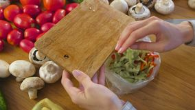 Woman`s hands put cutting red and green pepper in a plastic package for freezing on kitchen table. Woman`s hands put cutting red and green pepper in a plastic stock video