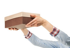 Woman's hands reaches out a cardboard box. Isolated on white Stock Images