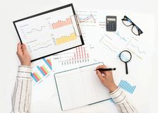 A woman`s hands record data from a report with graphs royalty free stock photo