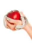 Woman's hands with red apple with measuring tape Royalty Free Stock Images