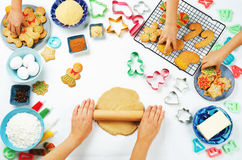 Woman`s hands roll ginger dough with kids hands, Gingerbread coo Royalty Free Stock Photo