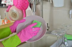 Woman`s hands in rubber gloves washing a plate royalty free stock photos