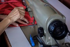 Woman`s hands sewing fabric  repairs on old sewing Stock Image