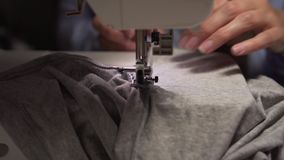 Woman`s hands sewing with a sewing machine. Women`s hands sew on a sewing machine. Fashion, creation and tailoring. Closeup of a young woman`s hands sewing with stock video footage