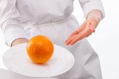 Woman's hands showing ripe orange on plate Royalty Free Stock Photography