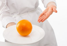 Woman's hands showing ripe orange on plate Stock Image