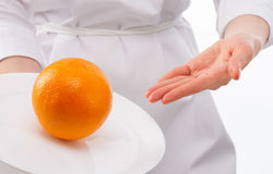 Woman's hands showing ripe orange on plate Stock Photo