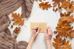 Woman`s hands sign an envelope with a greeting card. Top view. Autumn time concept.  Royalty Free Stock Photo