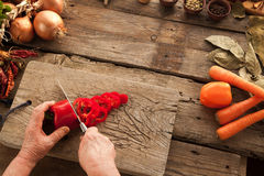 Woman`s hands slicing pepper on wooden board. Stock Photo