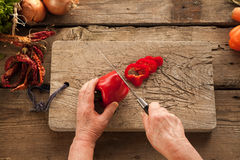 Woman`s hands slicing pepper on wooden board. Royalty Free Stock Photography