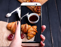 Woman`s hands with smartphone with the photo of breakfast Royalty Free Stock Image