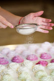 Woman`s hands sprinkling with icing sugar a zephyr Royalty Free Stock Photos