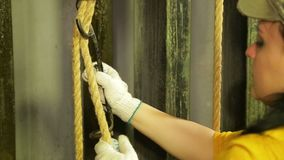 Woman`s hands of a stage worker in gloves puts the mount on a cable of a theater curtain. Close-up stock footage