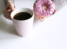Woman`s hands in sweater holding cup of coffee and donut on the wooden table. With copy space.Top wiev. Winter design. Feminine royalty free stock photos
