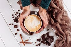 Woman`s hands in sweater holding cup of coffee on the white wooden table. Top view with chocolate and spices decor. Copy. Space stock photo