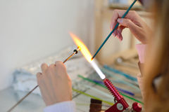 Woman's hands with tools for glass melting, lampwork, fire Royalty Free Stock Photo
