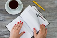 Woman`s hands turning a page in a notebook. Cup of tea and a pen royalty free stock photography