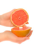 Woman's hands with two pieces of grapefruit Stock Photography