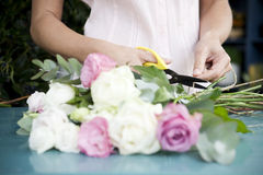 Woman's hands tying together a bouquet of pink and white roses stock image