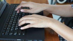 Woman`s hands typing on laptop computer THAI keyboard on wooden table stock video footage